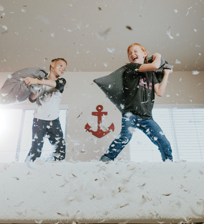 Children having a pillow fight on the bed
